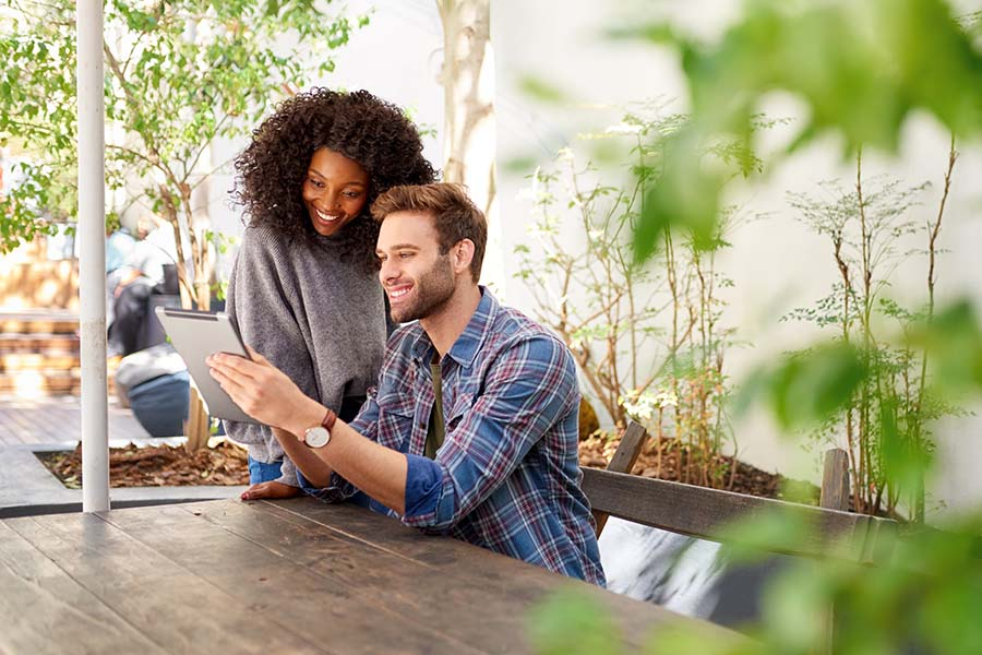 Client Center - Young Couple Smiling While Using a Tablet Together Outside While Sitting at a Picnic Table