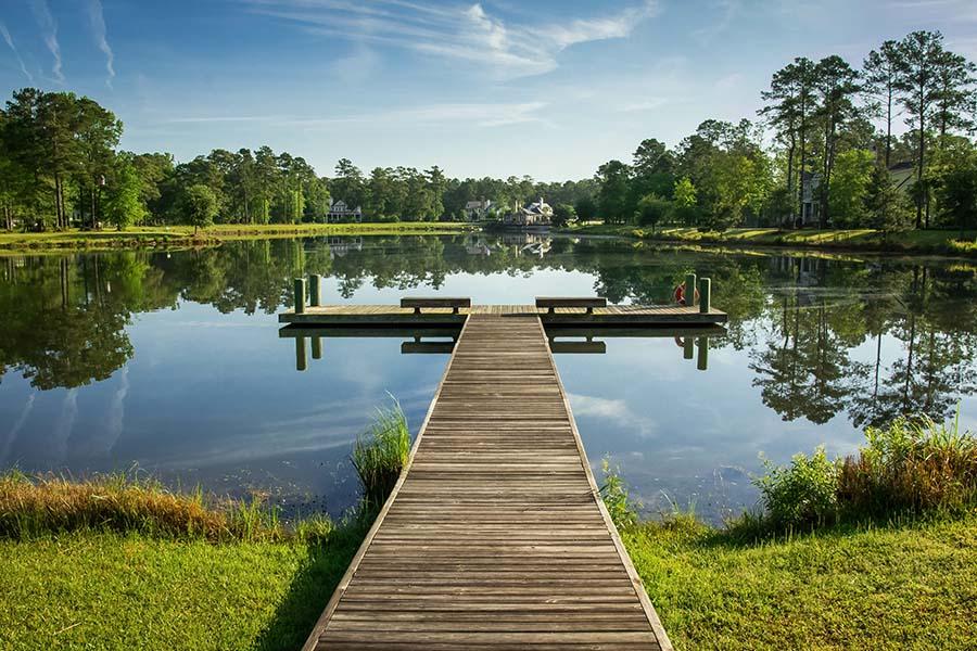 Moncks Corner, SC - Landscape View of a Pier Over a Still Lake with Blue Skies in Moncks Corner, South Carolina