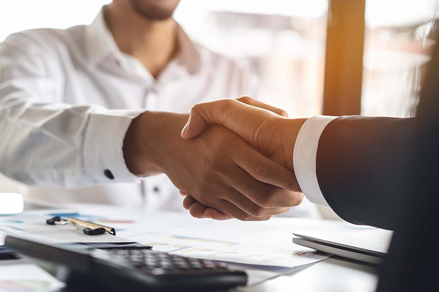 Our History - Closeup View of Business Partners Shaking Hands in an Office Setting