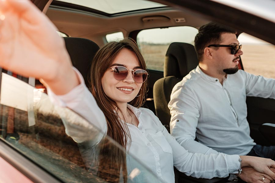 Blog - Young Couple Enjoying a Ride in a Red Car, Woman Waving Her Hand Out the Window